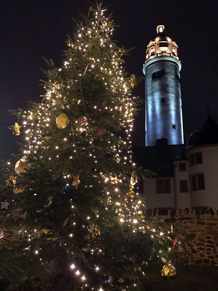 Der Höchster Geschichtsverein wünscht frohe Weihnachten und gibt einen Jahresrückblick auf 2019. Zu sehen ist der festlich geschmückte Weihnachtsbaum auf dem Höchster Schlossplatz, im Hintergrund der beleuchtete Schlossturm in der Höchster Altstadt.